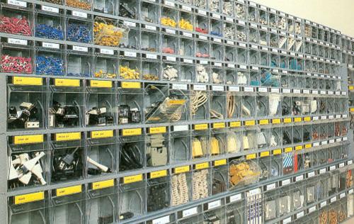 Regały z pojemnikami uchylnymi w magazynie elektrycznym